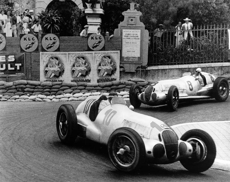 1937年のモナコグランプリにて、名物コーナーのロウズ・ヘアピンを駆け抜けるマンフレート・フォン・ブラウヒッチュとルドルフ・カラチオラのメルセデス・ベンツW125。