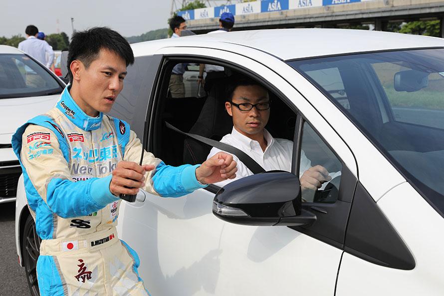 サーキット走行のインストラクターを務める社員ドライバーの水谷選手。シート合わせやステアリングの回し方、アクセル、ブレーキの踏み方など細かくレクチャーする