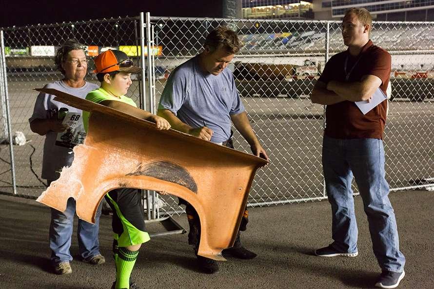 レース中に外れたパーツにサインをもらう子供も。サインしているのはロビーさん。お父さんやおばあちゃんも一緒にいて、親子3世代でレース観戦を楽しんでいる。実にうらやましい光景だ。