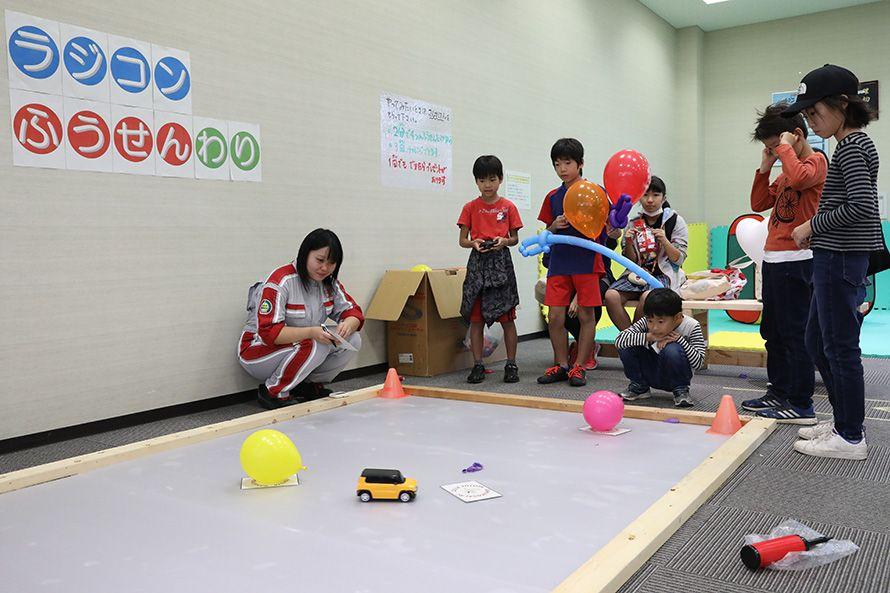 クルマ好きを増やそうと子供たちにラジコンのクルマで風船を割るゲームを開催