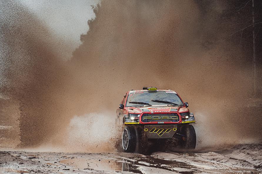 後ろが見えなくなるほど泥水を掻き上げ走るフォード・ラプター。