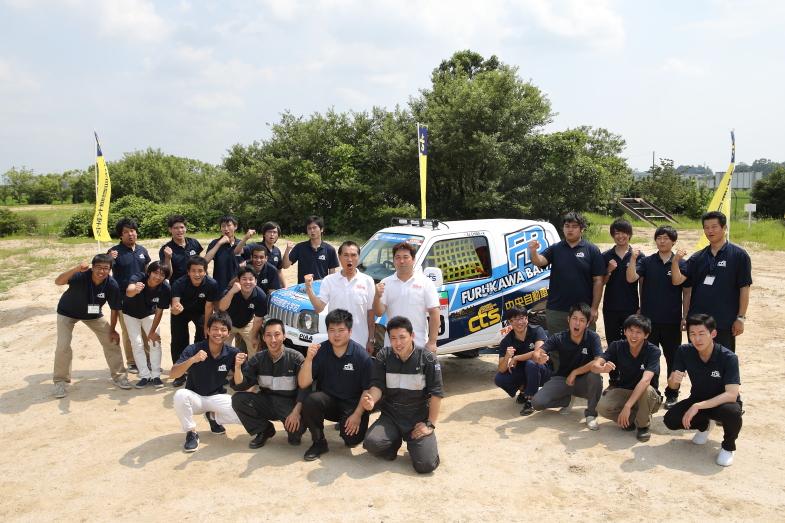 マシンを製作した20人の学生、教職員、そして篠塚・千葉両選手。最前列の4人の学生は現地に行きサービスを行う選抜メンバーだ