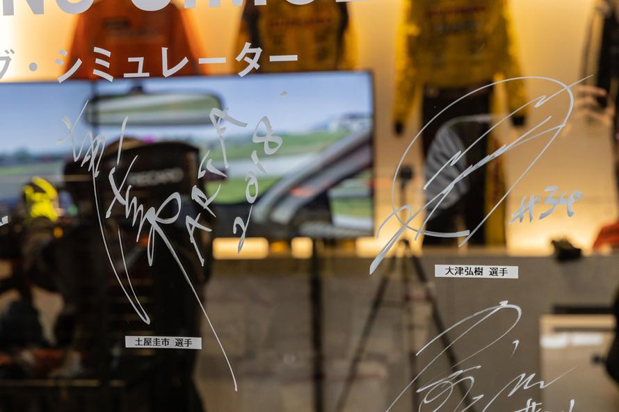 ガラスにはプロドライバーである土屋圭市さんや大津弘樹さんのサインが書かれている