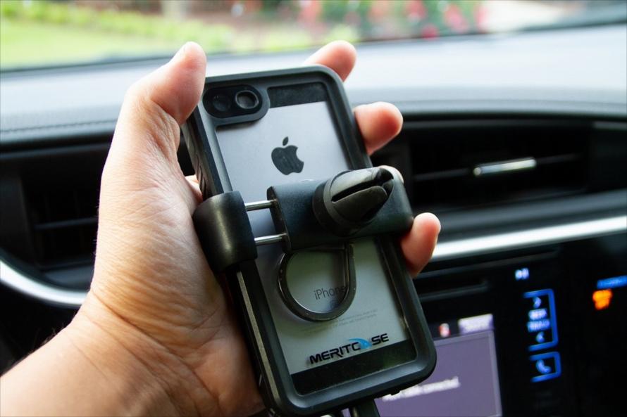 スマートフォン用車載フォルダーは非常に便利。エアコンの吹出し口に取り付けるタイプは、数ドルでガソリンスタンドで購入可能