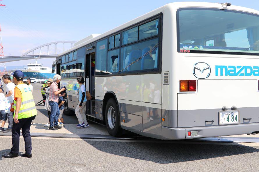 マツダ本社正面玄関で集合した参加者。見学する自動車専用船アクアマリンエース号までバスで移動した