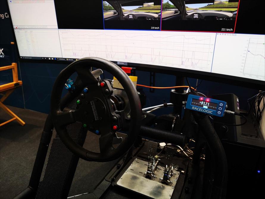 リアルのモータースポーツと同じく、タイム、ハンドルの切り方、加減速をデータロガー(ハンドル右横のRACELOGICという機械)で記録・分析してフィードバックしていく。「VBOX」ブースにて