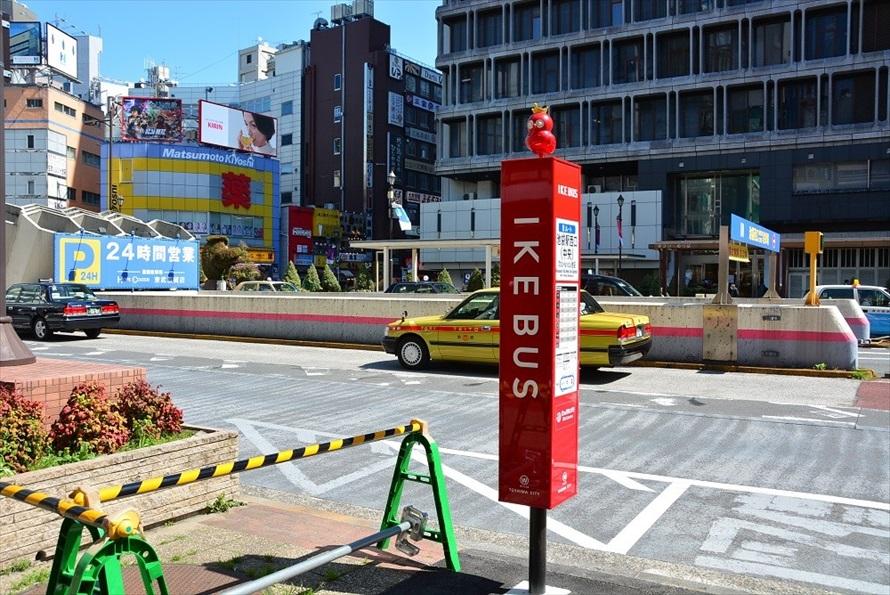 イケバスのバス停留所。テーマカラーの赤とフクロウのキャラクターが目を引く。