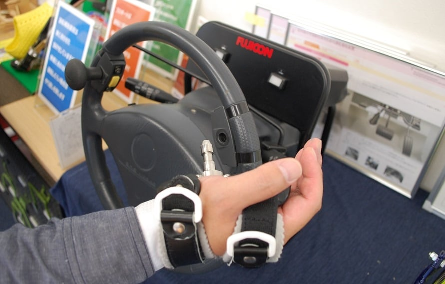 ステアリングの左手側に施されているのが「ステアリンググリップ」。手のひらで握るのが難しい人は、ノブの代わりに右手で使用しているグローブを選択できる