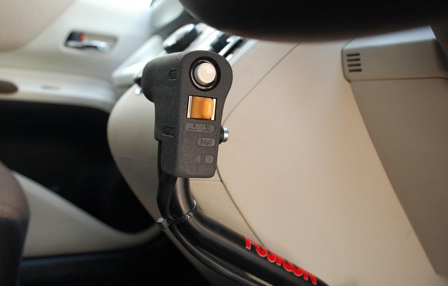 左手で操作する「手動運転装置」。押し込むことでブレーキペダルが踏まれ、手前に引くことでアクセルペダルが踏まれる。側面の白いボタンはブレーキロック、橙色のスイッチはウインカー、前方にある銀色のボタンがクラクションとなる