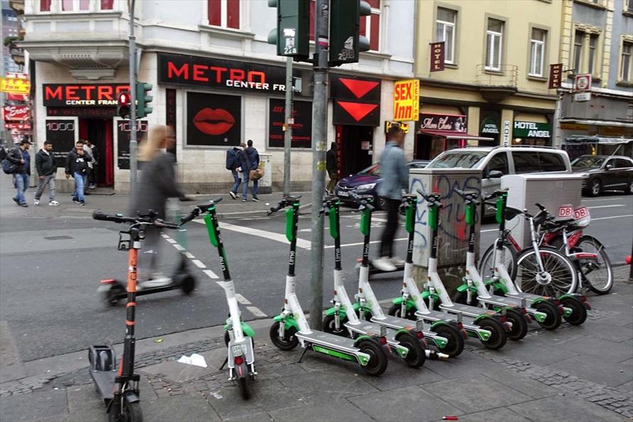 ドイツ/フランクフルトで見かけた電動キックスクーターのシェアリングサービス。その前を利用者が次々と通過していく(撮影:会田肇)
