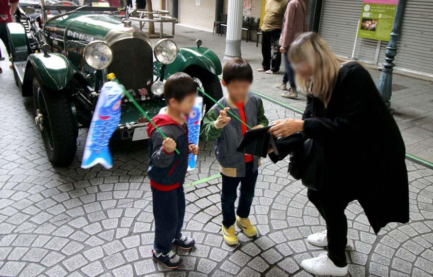 撮影した写真を確認する地元の子どもと外国人観光客