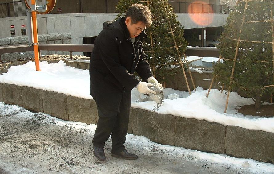 つるつる路面に直接まいていきます。画像提供:札幌市建設局土木部雪対策室計画課