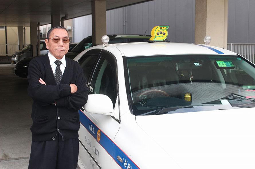 斎藤さんと愛車のクラウン。行灯の三つ星はマスターズの証で、個人タクシー最高位ドライバーの証だ