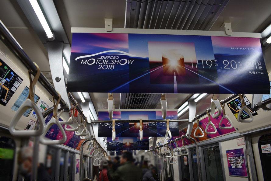 札幌ドームへ向かう地下鉄東豊線の車内。札幌モーターショー一色の車両が