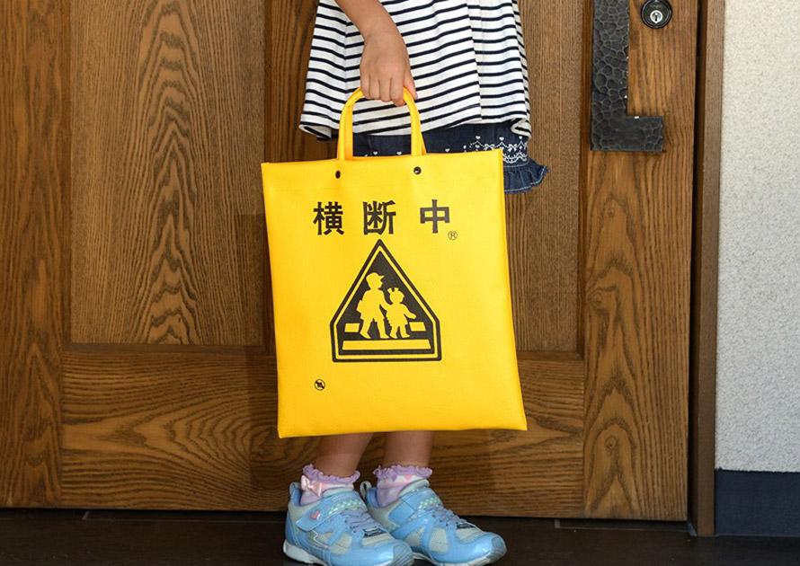「横断中」の文字が入る「横断バッグ」は、正方形より少し縦長の手さげバッグだ