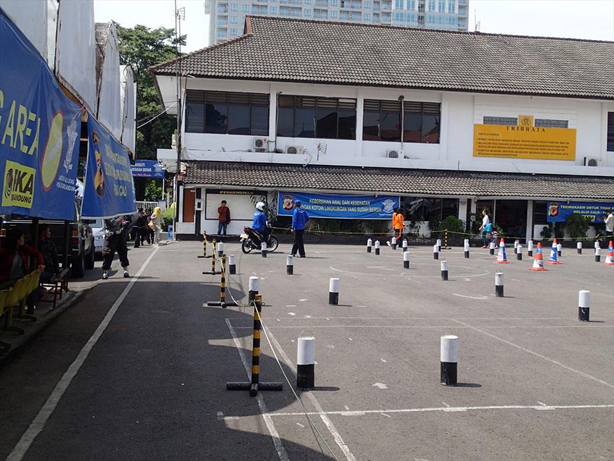 二輪車の実地試験コース。左から二本のパイロンの間がストレート、その向こうに八の字、右のパイロンがスラローム用