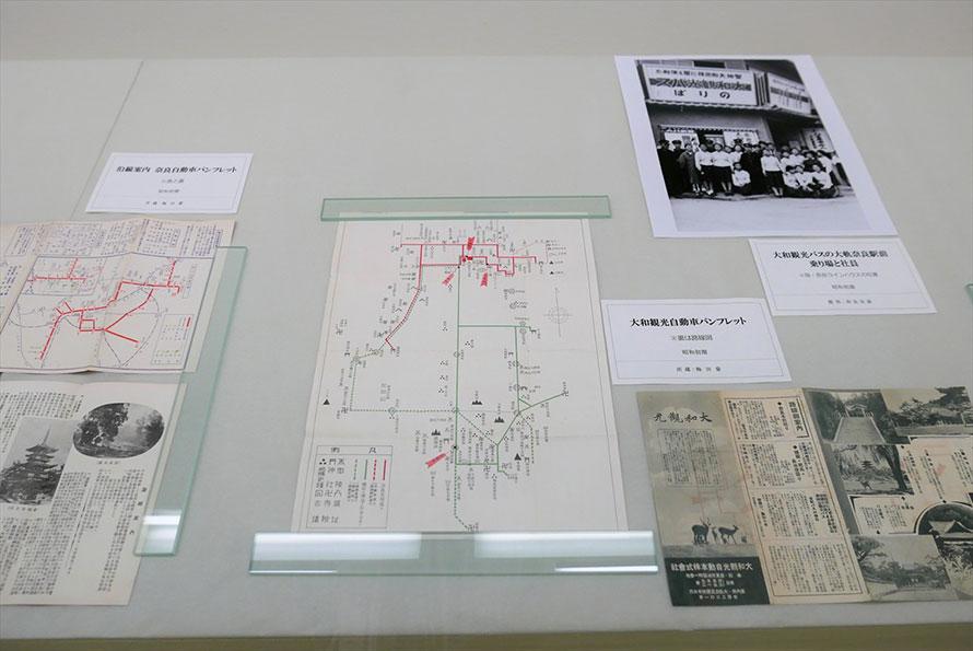 昭和初期の路線図、観光案内パンフレット、バス乗り場での社員の集合写真など。左が奈良自動車、右が大和観光自動車のもの。貴重な資料には個人所蔵のものも多い