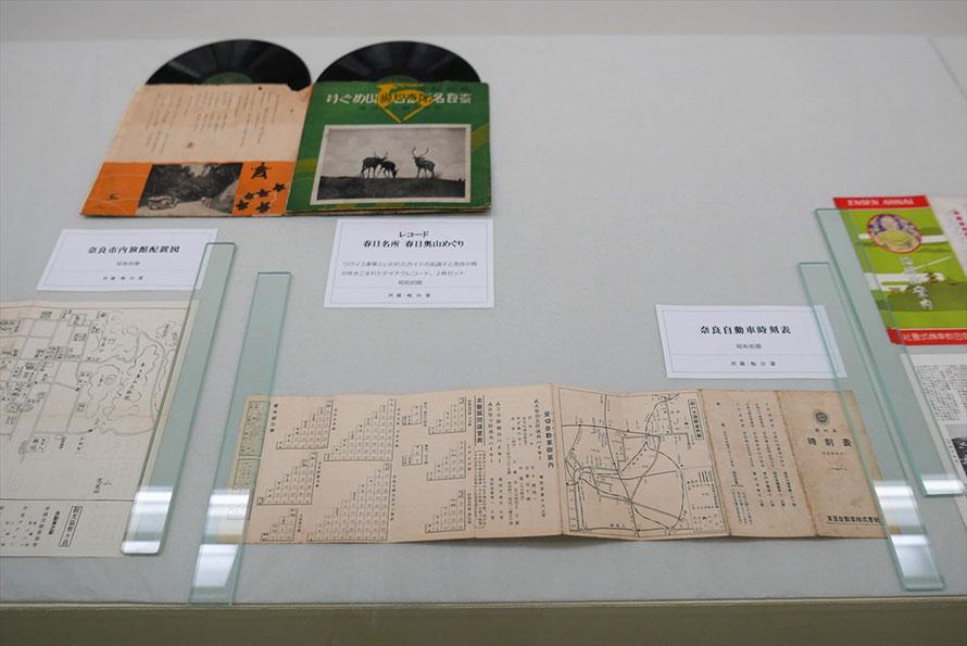 奈良自動車の時刻表・運賃表(手前)、春日奥山観光のガイドの名調子と奈良小唄が吹き込まれたレコード(奥)。どちらも昭和初期の貴重な史料