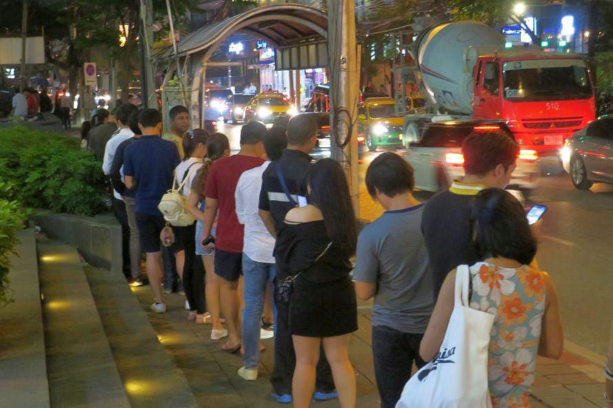 渋滞激しい金曜の夜に見かけた、バイクタクシーを待つ人の列。先頭付近で働いている係員は、乗客をさばきつつ、ほかの縄張りのバイクがお客さんを拾わないように管理するのも仕事の一つなのだとか。