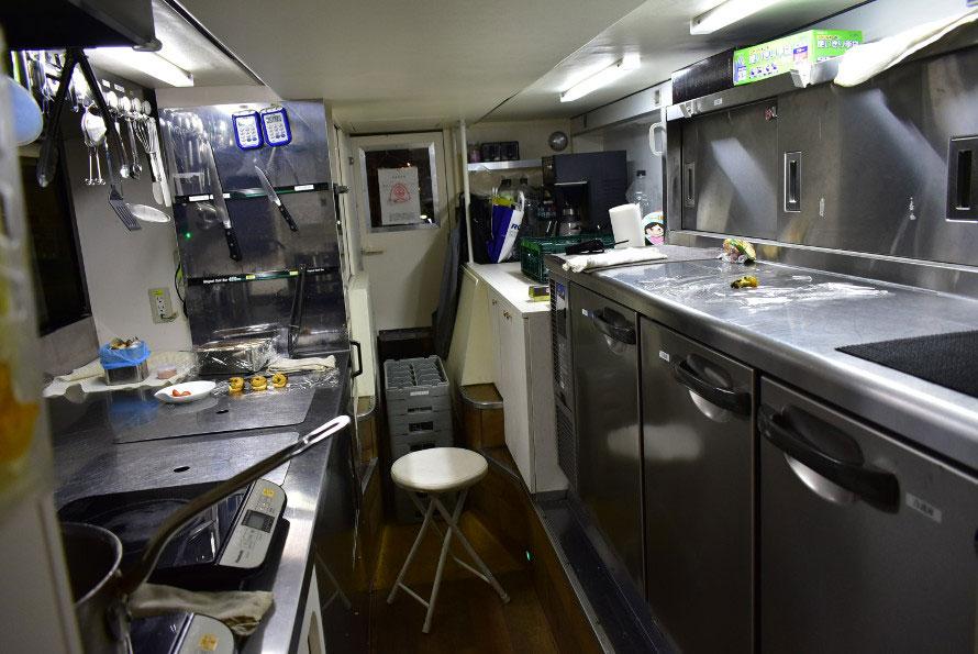 コンパクトながら機能的なキッチン。キッチンツールはマグネットで固定、食器棚はクルマの揺れにも開かないようにストッパーがつき、走行中でもスムーズに調理ができる工夫がされている。