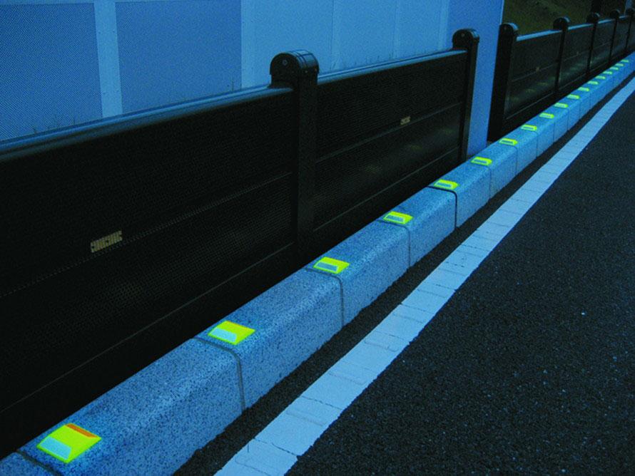 縁石の上に貼り付けるタイプの道路鋲(樹脂製)