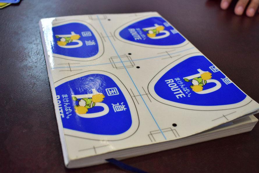 中嶋さんの手元には標識デザインのシートを貼ったノートが