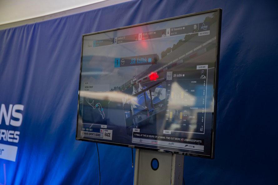 ブース内のモニターにレースの様子が映し出されている。わかりにくいが、タイヤや燃料などの損耗率が表示されている。