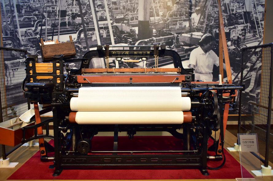 繊維機械館の初めに展示されるG型自動織機の第1号機。機械遺産としても認定されている。よこ糸のシャットルが自動交換され、たて糸が切れたら即座に運転が停止されるという仕組みが盛り込まれ、不良品を後工程に渡さず工場生産性を飛躍的に上げる画期的な発明品だった