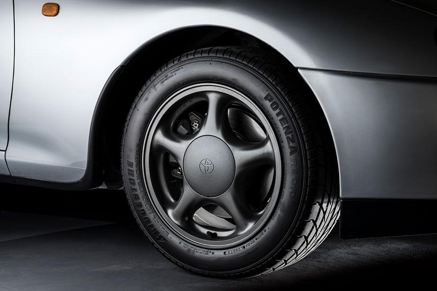 超扁平タイヤと軽量な専用アルミホイール、その奥にあるダブルウィッシュボーンサスが、乗り心地の良さと操縦安定性を高いレベルで両立している