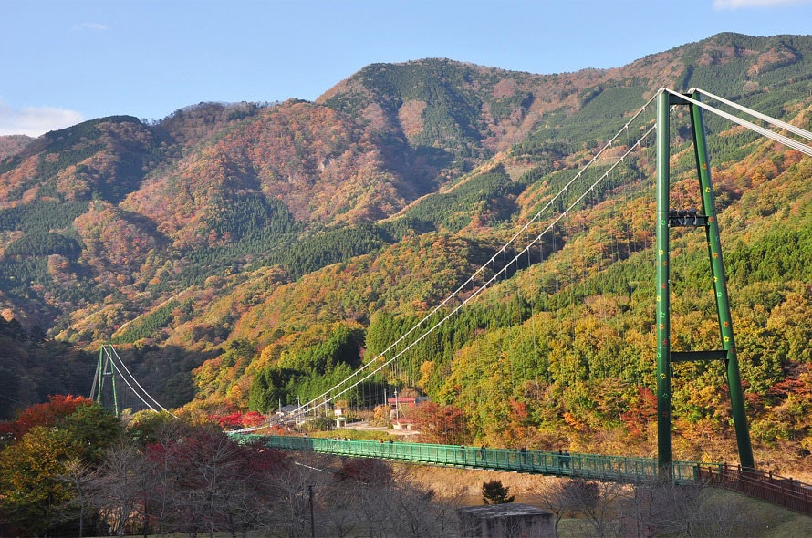 雄大さが魅力のもみじ谷大吊橋。入口には休憩施設「森林(もり)の駅」があり、恋人の聖地にちなんだグッズなどを販売。