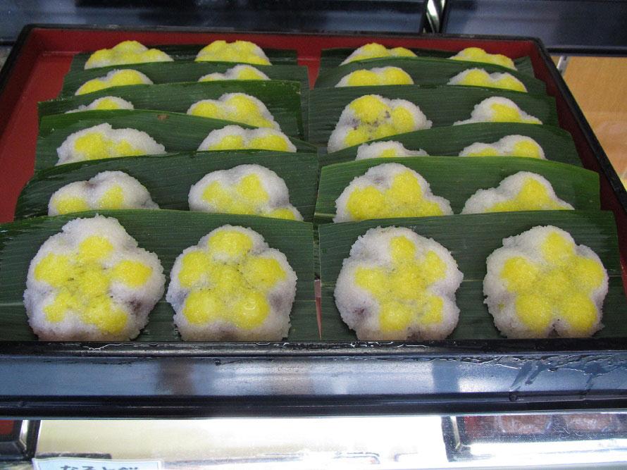 しあんを道明寺粉で作ったもちで包み、成型して蒸し器へ。蒸し上がったら笹の葉の上において完成。