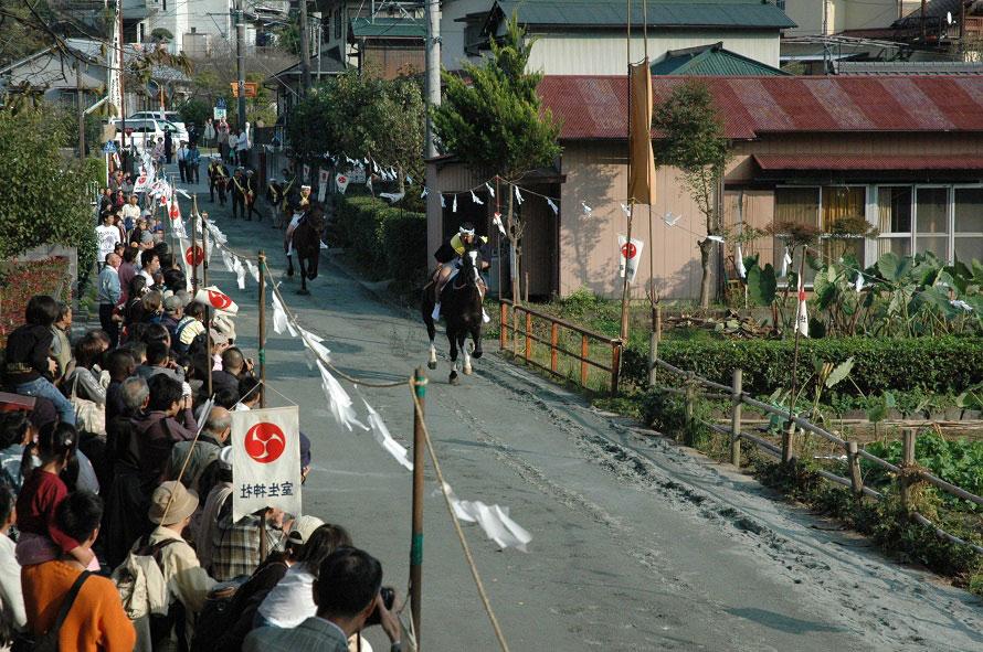 流鏑馬は「馬場駆け」から始まる。法被姿の騎者が馬に乗り、2頭で馬場を一往復。