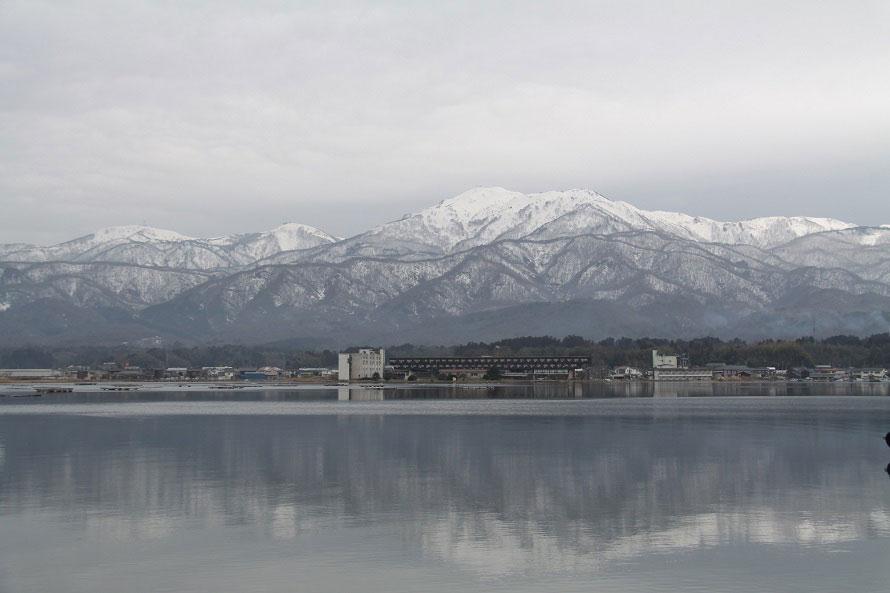雪をかぶった金北山を背に、水をたたえる加茂湖。湖岸は遊歩道やサイクリングロードが整備されている。