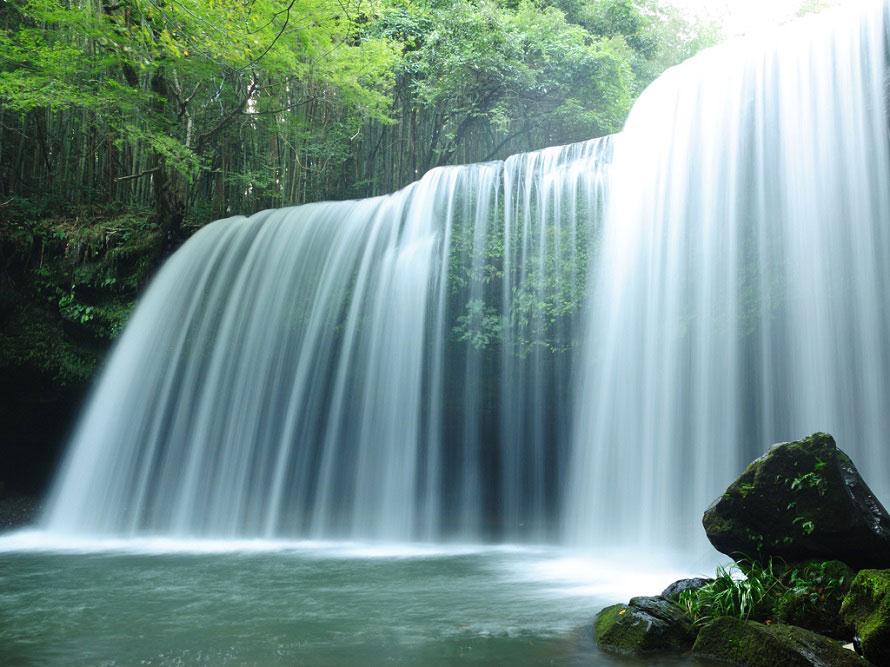 約9万年前の巨大噴火によりできたという鍋ヶ滝。長い年月をかけて現在の形となった。滝の裏側や川の対岸に立ち入ることもできるが、足元には十分気をつけて。