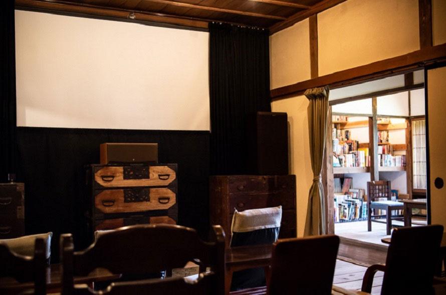 スクリーンは横幅3.6m(作品により映写サイズは異なる)。上映作品に合わせた「今月の本棚」コーナーも好評。