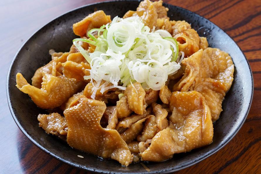 ヒナ鶏の皮を使った丸万食堂の鳥モツはネギがたっぷり。モツ単品500円、「モツ定食」750円。