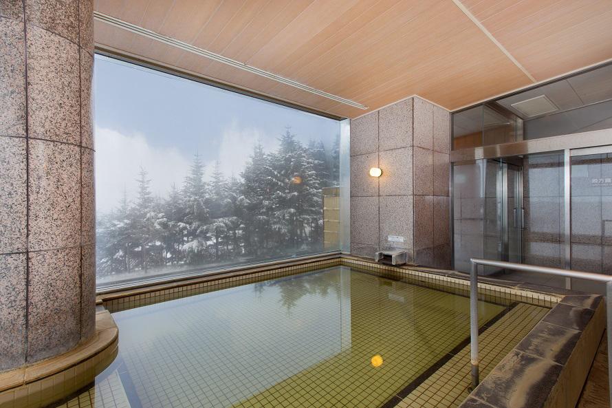 大浴場の大きな窓からも自然豊かな風景を一望。冬は雪見風呂を楽しもう。