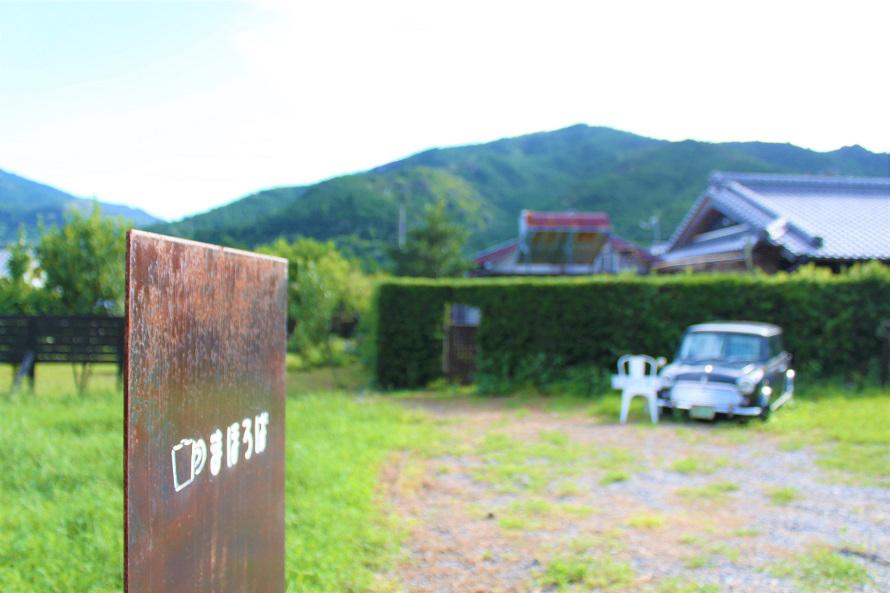「Cafe まほろば」は、山々に囲まれた静かなロケーション。店の前のミニクーパーには営業カレンダーとメニューが飾られている。