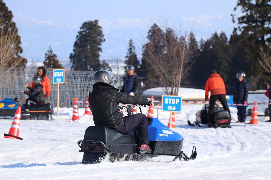 スノーモービル体験はお父さんにも人気。小学生は、インストラクターと同乗する。
