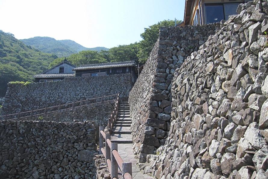 整然と積まれた石垣が軒の高さほどまで及ぶ。坂道を登る際は足元に気をつけて。