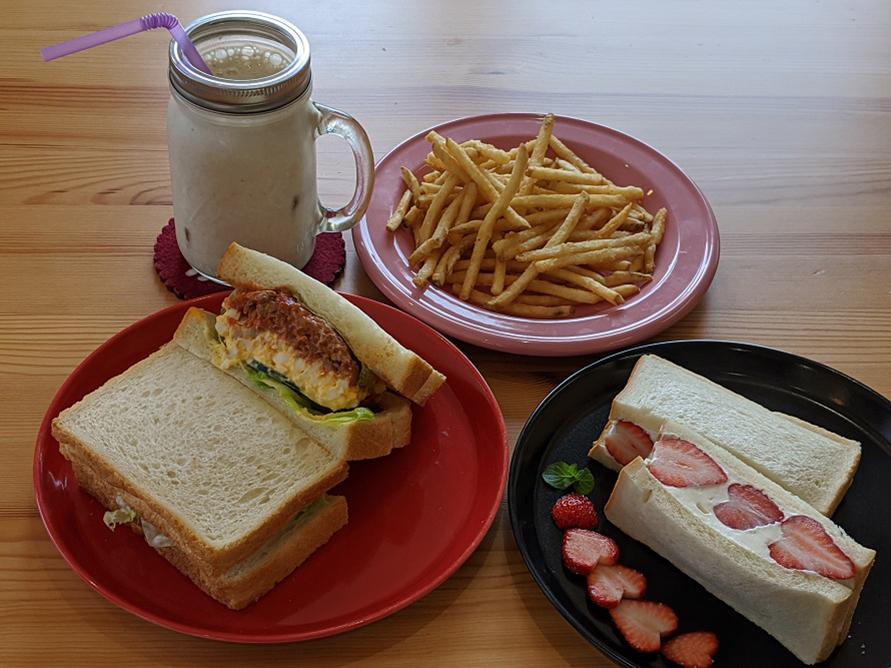 (写真左下から時計回りに)「ミートソースと卵のサンドイッチ」620円、「バナナミルク」450円、「フライドポテト」300円、「季節のフルーツを使用したフルーツサンド」(写真はいちごサンド)600円。サンドイッチ、ドリンク、ポテトをセットにすると150円割引。