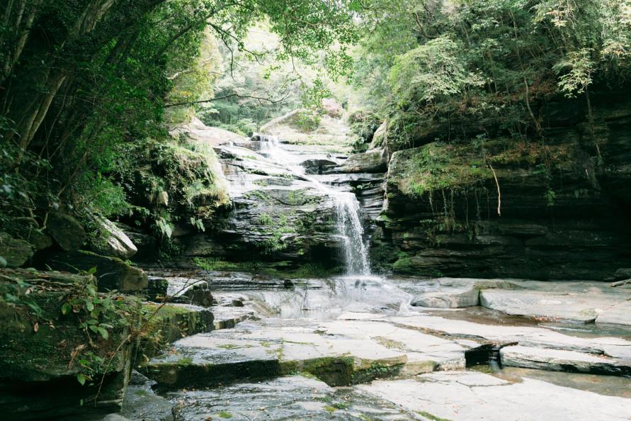 「つがね落としの滝」は深い緑に覆われているため日陰も多く、夏でもあまり日焼けを気にせずに済みそう。滝の左右までゴツゴツした巨岩が迫る。