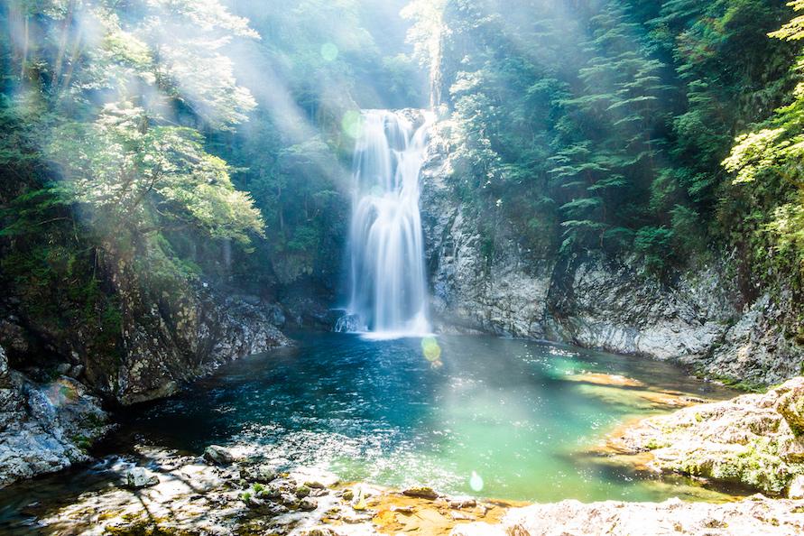 木々の間から光が差し込み、幻想的な美しさの堂倉滝。エメラルドグリーンの色は日によって変化する。