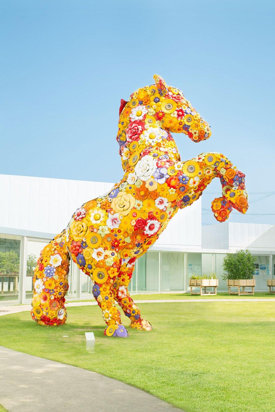 高さ5.5mのカラフルな馬の像。官庁街通りとつながる屋外イベントスペースに展示されている。チェ・ジョンファ《フラワー・ホース》 撮影:小山田邦哉
