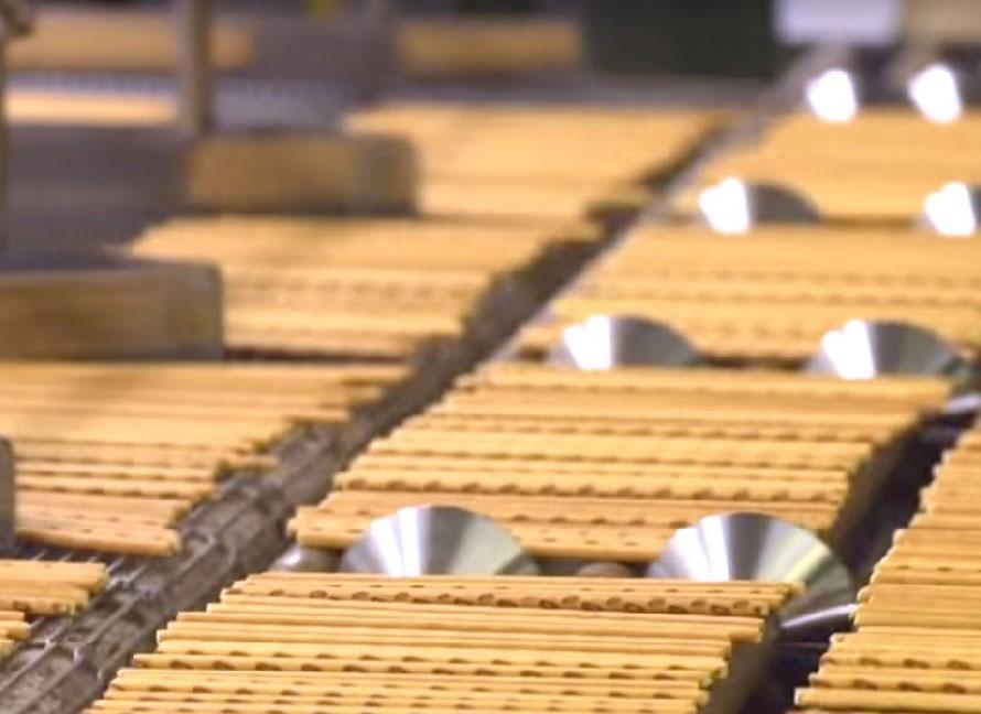 こちらはプリッツ。原料の混合から、仕上げ・包装までの生産ラインは長さ100mにも及ぶ。