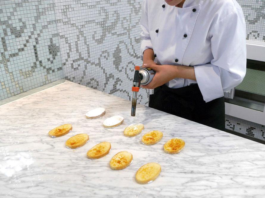 オーブンに入る直前のガトーラスクの表面にたっぷりと粉砂糖をまぶし、バーナーで焼きつけている様子。