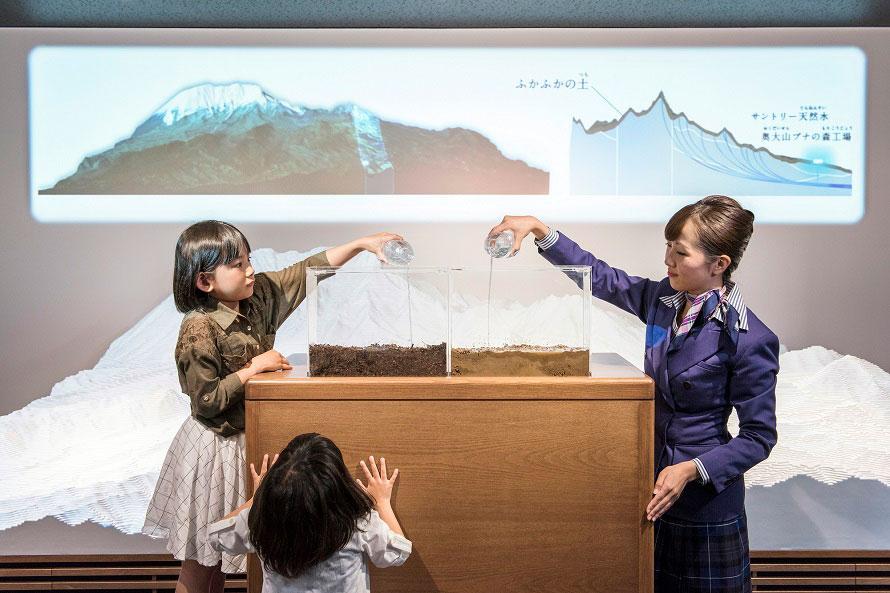 硬い土とふかふかの土、それぞれに水を通してどちらが水を多く蓄えられるか比べる実験に、興味津々の子どもたち。