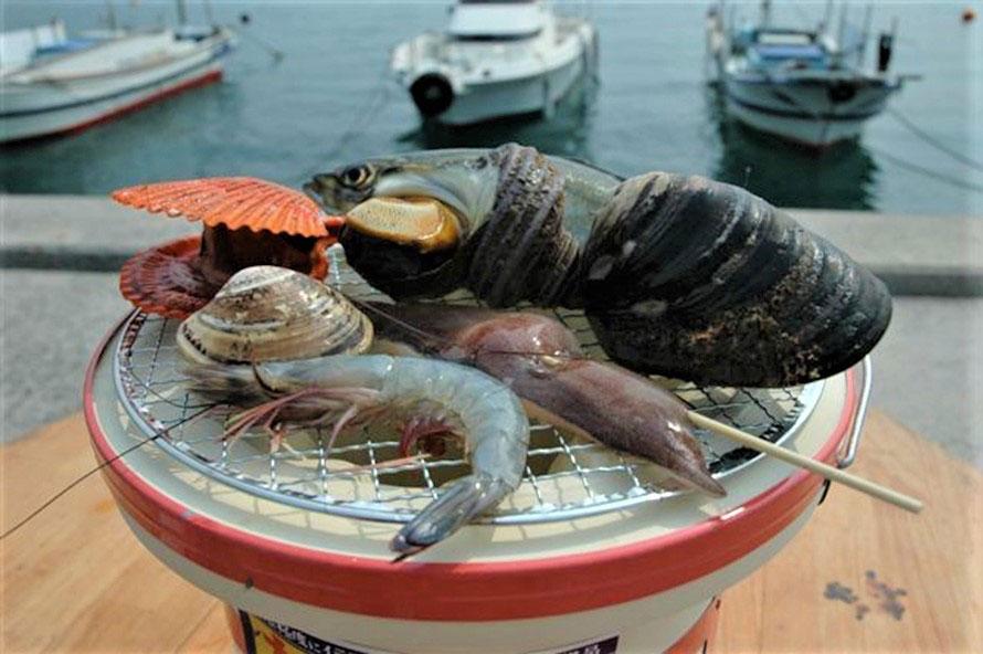 七輪バーベキューでは、サザエ、瀬戸貝、ヒオウギガイ、ハマグリ、エビ、イカほか、季節により色々な海鮮が楽しめる(魚介類の値段は時価)。生きたままの食材を、豪快に焼いて食べよう。