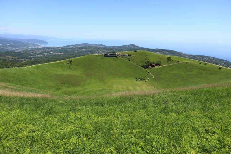 山頂から見た噴火口。お鉢の反対側に登山リフト乗り場があり、その先に太平洋が見える。