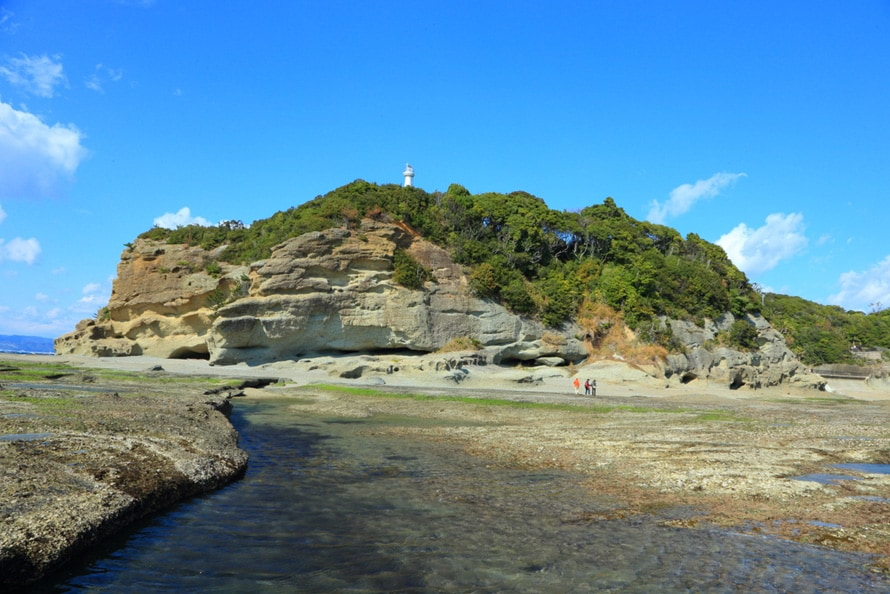 公園の下、岩礁から眺める番所鼻灯台。亜熱帯植物、熱帯植物が生い茂っている。